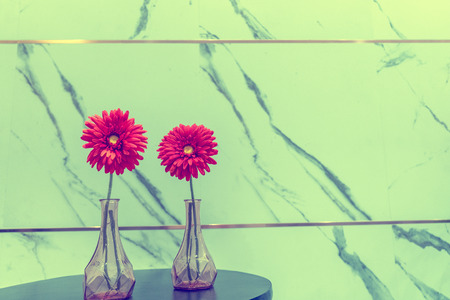 Red flowers in vase on marble wall background