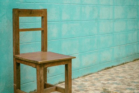 Old wooden chair on blue wall background Stock Photo