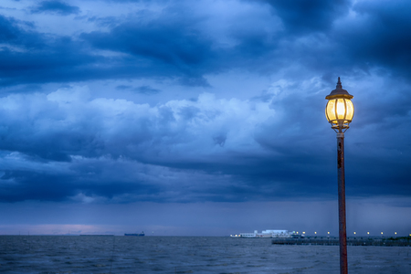 Light Post at nigth near sea with stom background