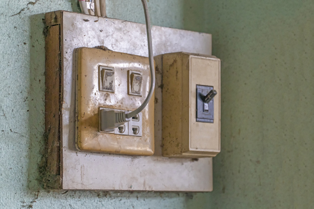 The old electrical plug next to the cream wall. Editorial
