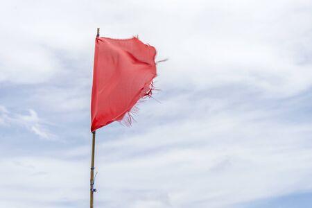 Red flag warning flags wind blue sky Reklamní fotografie