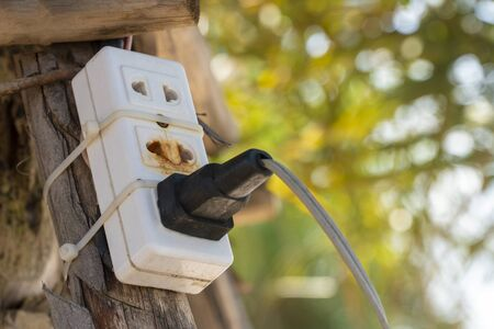 The old electrical plug next to the cream wall. Stock Photo