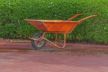 Cement cart red In the garden on green background