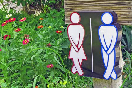 Male Female Toilet Symbol located in the flower garden nature Stock Photo