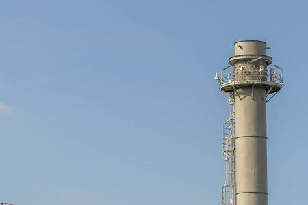 Electric plant chimney against the blue sky background, Power plant flue, copy space