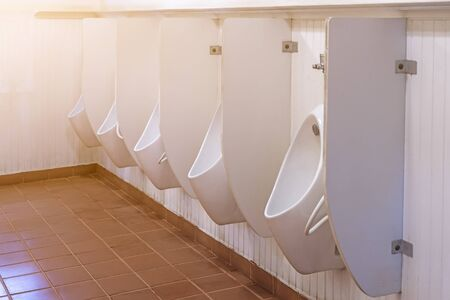 Many white urinals in the male bathroom modern style used in public health