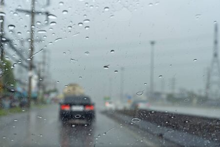 Driving in the rain there are water drops in the glass.and  see a black car blur