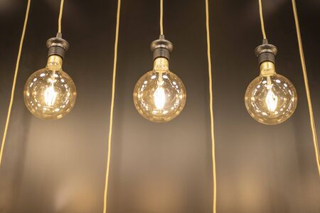 3 incandescent bulbs hanging with wires, Abstract background