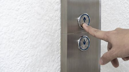 Finger press the lift button, Push the elevator button up, body part Stock Photo