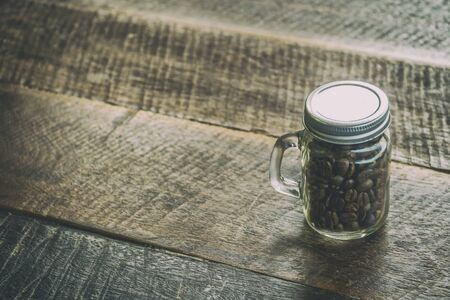 Coffee beans in bottles placed on the old table wood brown color have copy space