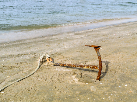grapnel: Old anchor Boats tied at the beach
