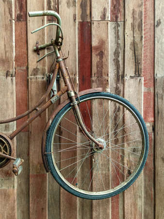The old style bicycle is parked. Beside the old wooden