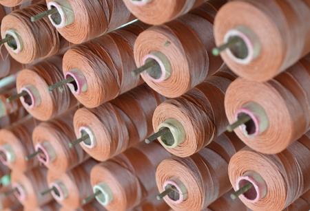 Brown yarn cone mounted in a fabrics factory.