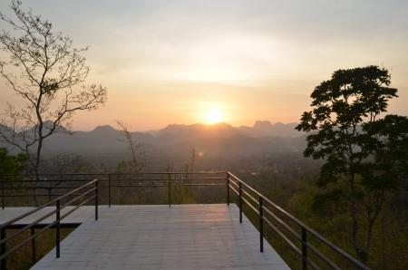 indietro albero e paesaggio di montagna al tramonto photo