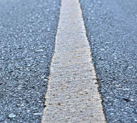 Asphalt road texture with yellow stripe photo