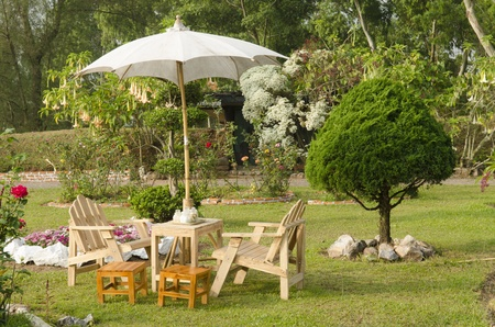 beautiful garden with flower and wooden table and chairs - home decoration photo