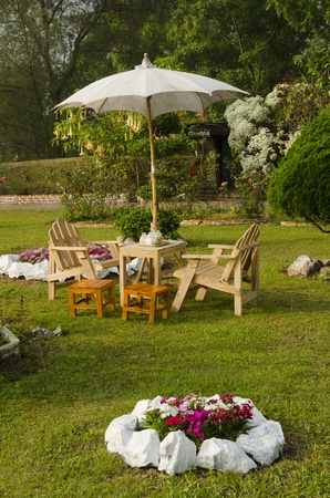 flower garden path: dining table with chairs and parasol in the shade in a lush garden