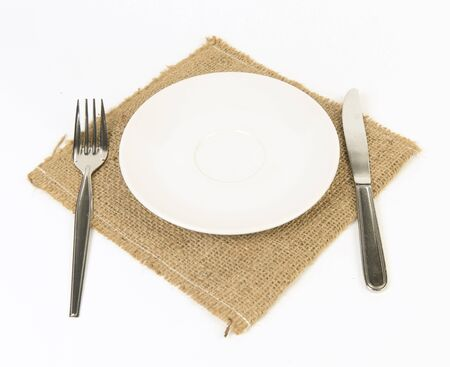 Dinner place setting  A white plate with silver fork, knife and Napery isolated on white background  photo