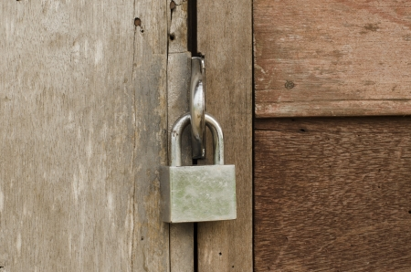 The padlock locking the wooden door photo
