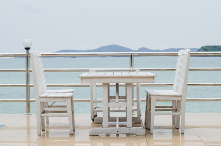 Dining table on a beach close to the ocean Banco de Imagens