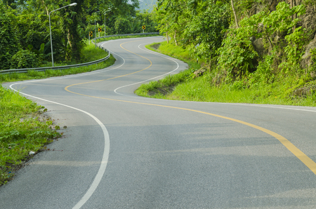 sharp curve: Asphalt road sharp curve along with tropical forest zigzag ahead. Stock Photo