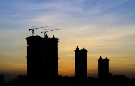 maneuverable: mobile crane lifting generator, silhouettes at sunset