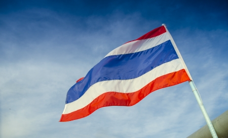 Image of waving Thai flag of Thailand with blue sky background. photo