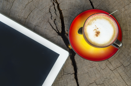 digital tablet and coffee cup on wooden table photo