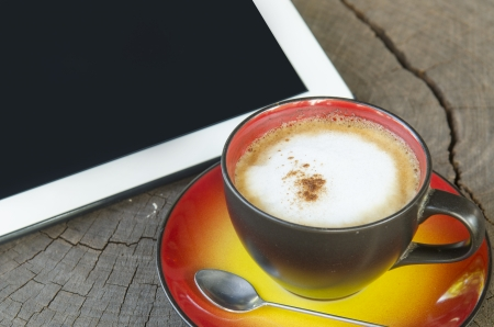 digital tablet and coffee cup on wooden table Stock Photo - 24616770
