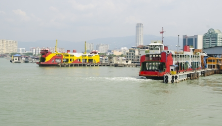 Yellow ferry with mountain and cloudy sky at background in Georgetown, Penang, Malaysia Stock Photo