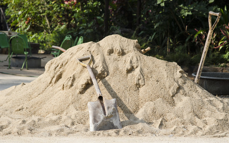 Pile of sand and shovel for construction photo