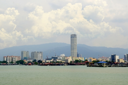Penang cityscape with boats on ocean and skyscraper in Malaysia, Asia.