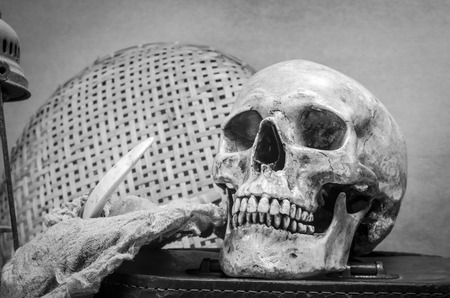 old items: Still life with human skull with old Items in black and white Stock Photo