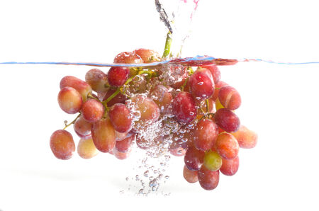 fresh grape dropped into water with splash isolated on white photo
