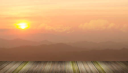 Beautiful sunlight over moutain with wood planks floor photo