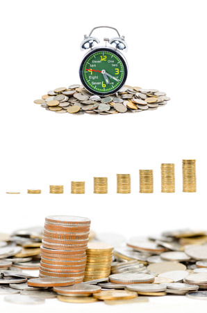 Alarm clock standing with coins isolated on white background photo
