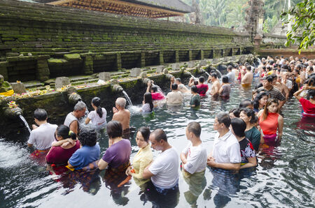 cleanse: BALI, INDONESIA - JUNE 9: Balinese Hindu families come to the sacred springs of Tirta Empul in Bali, Indonesia to pray and cleanse their soul on June 9, 2014.