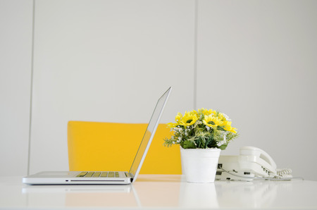 laptop telephone and flower in vase on desk photo