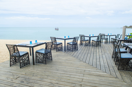 Table and chair setting on the tropical beach with blue sky photo