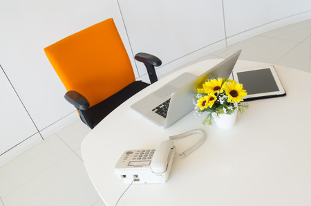 Modern creative workspace with computer and orange chair. The office of a creative worker. photo