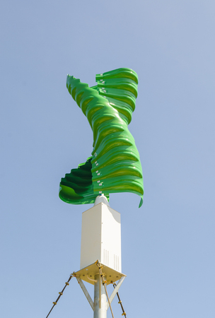 Wind turbine in the vertical spiral shape against blue sky background photo