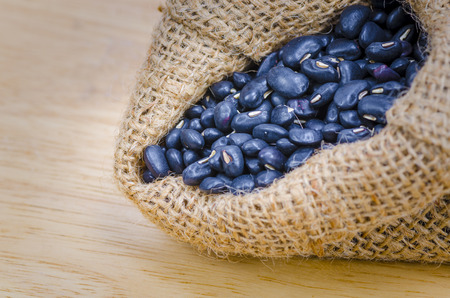Beans in sack, on wood background photo