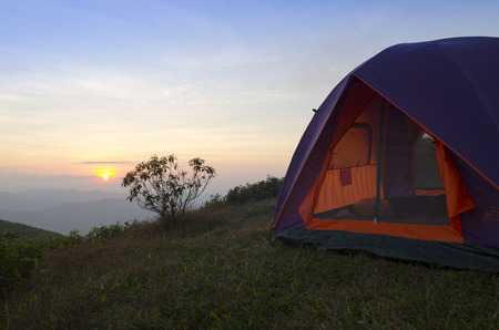 recreation area: recreation area and camp with tent, sunset time with rising sun near high mountain lake Stock Photo