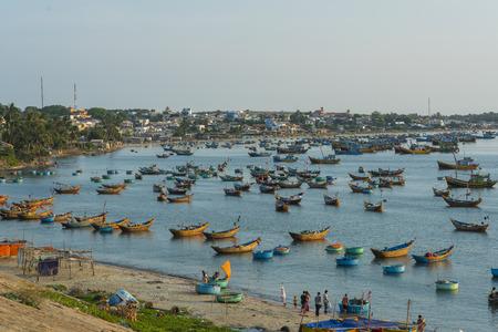 ne: MUI NE, VIETNAM - FEBRUARY 01, 2016 : Fishing village and colorful fishing boats near Mui Ne at a sunny day