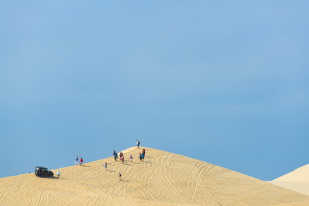 Mui ne city, Vietnam - JANUARY 18: Unidentified people sitting on the sand dune in morning on January 18,2016 at Red sand dune, Mui ne, Vietnam Editöryel