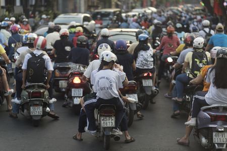 3 5: HO CHI MINH CITY, VIETNAM - FEBRUARY 1, 2016: traffic jam with a congestion of scooters and people with colorful helmets. There are approximately 340,000 cars and 3,5 million motorcycles in the city.