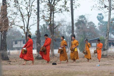 distributing: Luang Prabang, Laos - circa December 2015: Traditional Alms giving ceremony of distributing food to buddhist monks on the streets of Luang Prabang, Laos