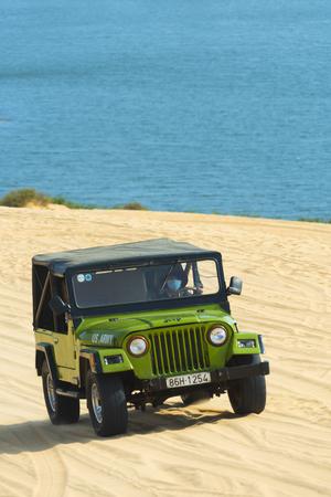 ne: MUI NE - VIETNAM, JANUARY 18, 2016 : Tourists enjoy on the desert by jeep car in Mui ne, January 18, 2016