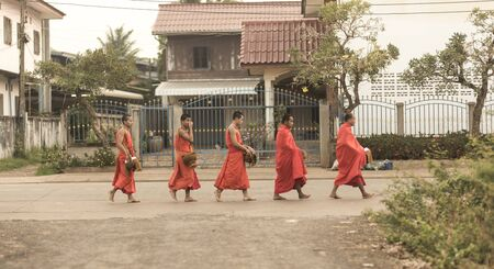 limosna: Luang Prabang, Laos - alrededor de diciembre de 2015: Limosna tradicional ceremonia de entrega de la distribución de alimentos a los monjes budistas en las calles de Luang Prabang, Laos