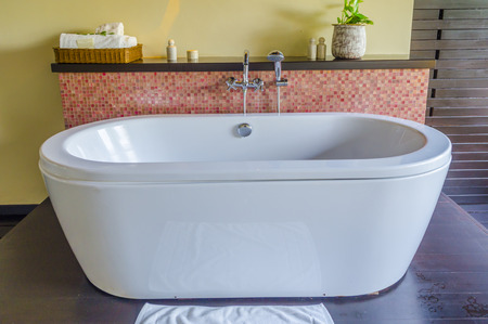 free standing: free standing contemporary ceramic bath tub and stone tile wall